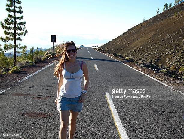 Portrait Of Happy Woman Standing On Road Against Sky