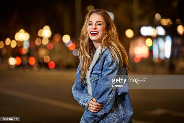 Portrait of happy woman standing on road at night