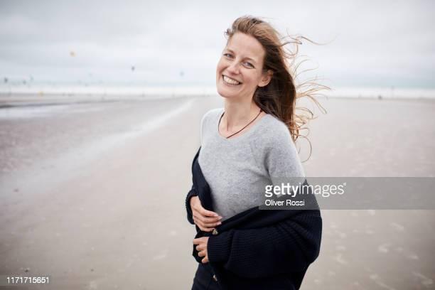 portrait of happy woman standing on the beach - cardigan photos et images de collection