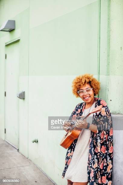 portrait of happy woman strumming guitar while leaning on wall - plucking an instrument stock pictures, royalty-free photos & images