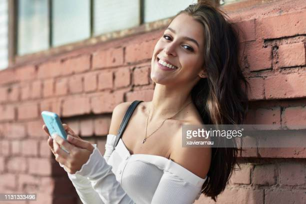 portrait of happy woman using mobile phone in city - off shoulder stock pictures, royalty-free photos & images