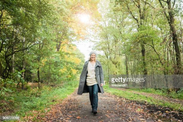 portrait of happy woman walking in the forest in autumn - gehen stock-fotos und bilder