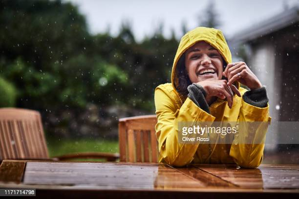 portrait of happy woman wearing raincoat during heavy rain in garden - joy stock pictures, royalty-free photos & images
