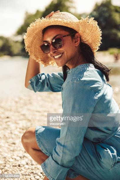 portrait of happy woman wearing straw hat and sun glasses on the beach - denim dress stock photos and pictures