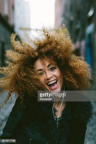 Portrait of happy woman with afro hearing music with earphones