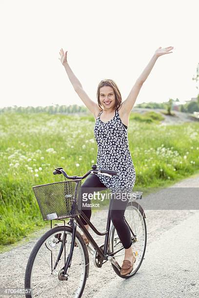 portrait of happy woman with arms raised cycling on country road - hands free cycling stock pictures, royalty-free photos & images