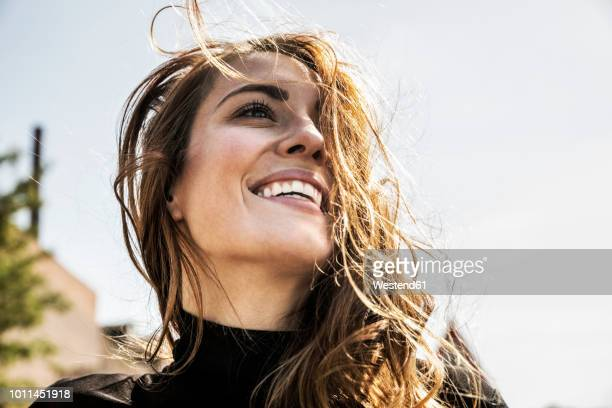 portrait of happy woman with blowing hair - sonreír fotografías e imágenes de stock