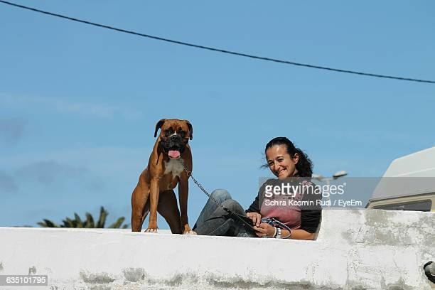 Portrait Of Happy Woman With Boxer On Retaining Wall Against Sky