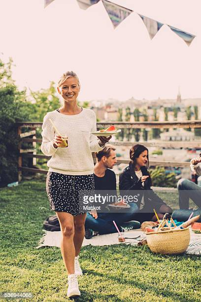 Portrait of happy woman with breakfast walking at rooftop party