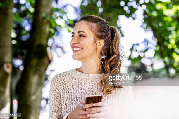 portrait of happy woman with cell phone - ponytail stock pictures, royalty-free photos & images