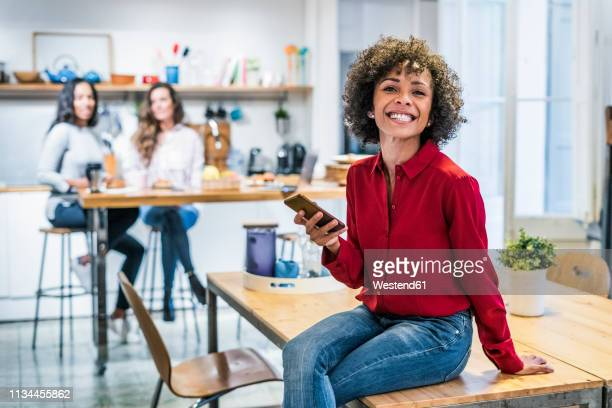 portrait of happy woman with cell phone sitting on table - black blouse stock pictures, royalty-free photos & images