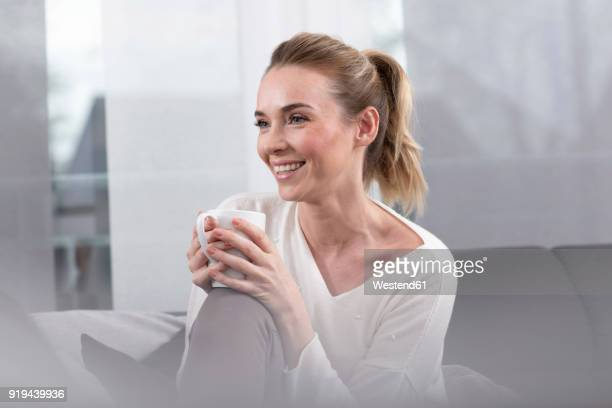 Portrait of happy woman with coffee mug at home