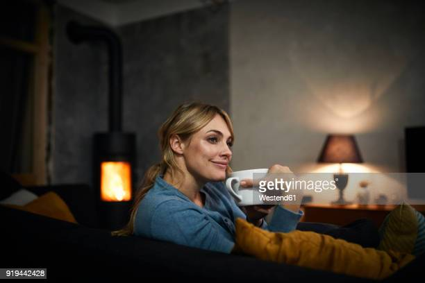 portrait of happy woman with cup of tea relaxing on couch at home in the evening - hot tea stock pictures, royalty-free photos & images