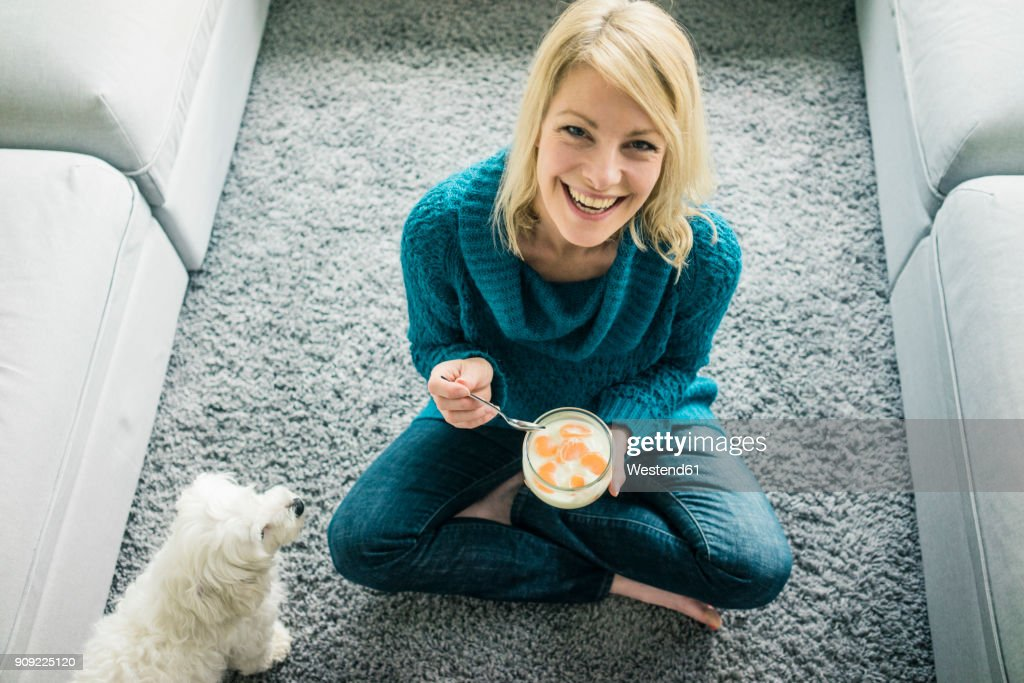 Portrait of happy woman with dog eating fruit yoghurt in living room : Stock Photo