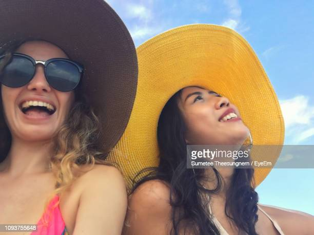 portrait of happy woman with friend at beach - sun hat stock pictures, royalty-free photos & images