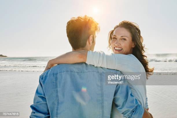 Portrait of happy woman with her partner on the beach