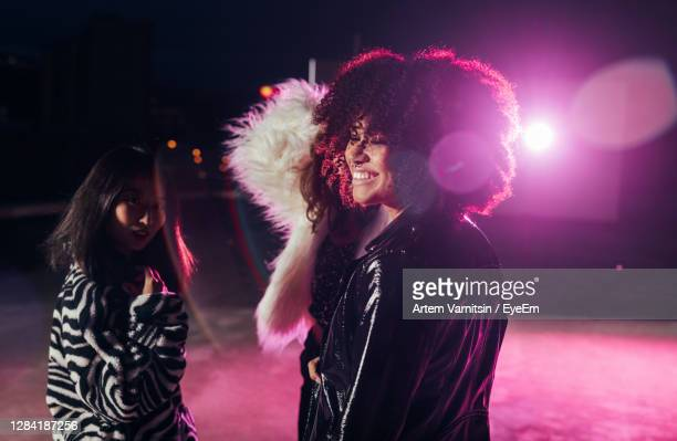 portrait of happy woman with illuminated lights at night - nightclub stock pictures, royalty-free photos & images