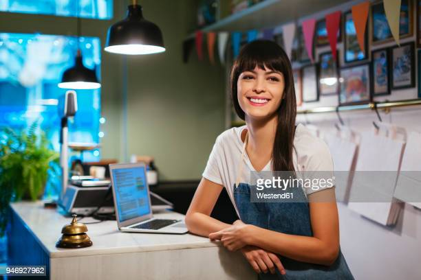 Portrait of happy woman with laptop in a store