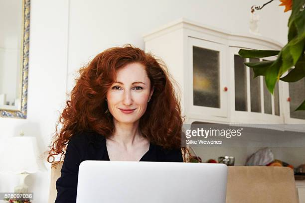 Portrait of happy woman with laptop in kitchen