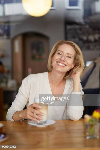 portrait of happy woman with latte macchiato in a coffee shop - blonde glasses stock-fotos und bilder