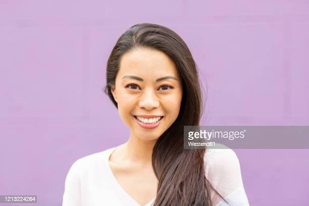 portrait of happy woman with long brown hair against purple background - brown hair photos et images de collection