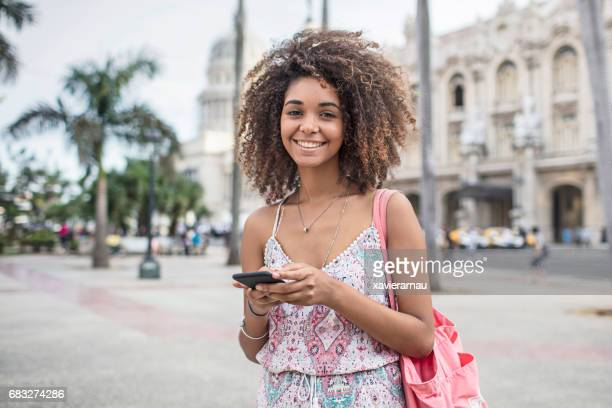 Portrait of happy woman with mobile phone in city
