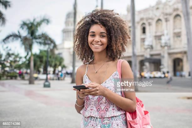 Portrait de femme heureuse avec le téléphone mobile dans la ville