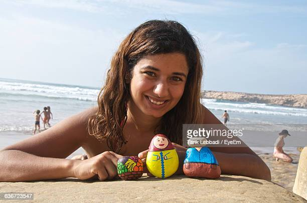 Portrait Of Happy Woman With Painted Rocks At Beach