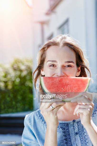 Portrait of happy woman with slice of watermelon outdoors