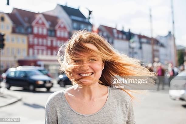 Portrait of happy woman with windswept hair on city street