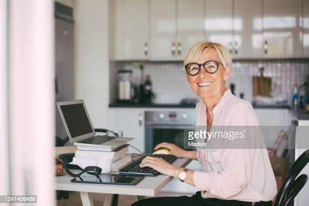 portrait of happy woman working at home - seulement des adultes photos et images de collection