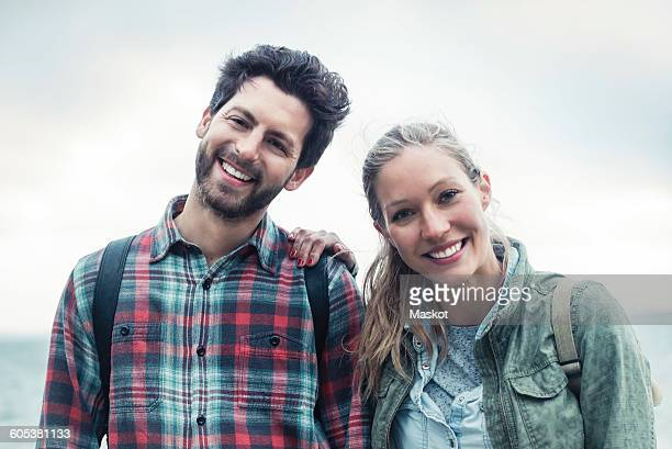 Portrait of happy wonderlust couple standing against sky