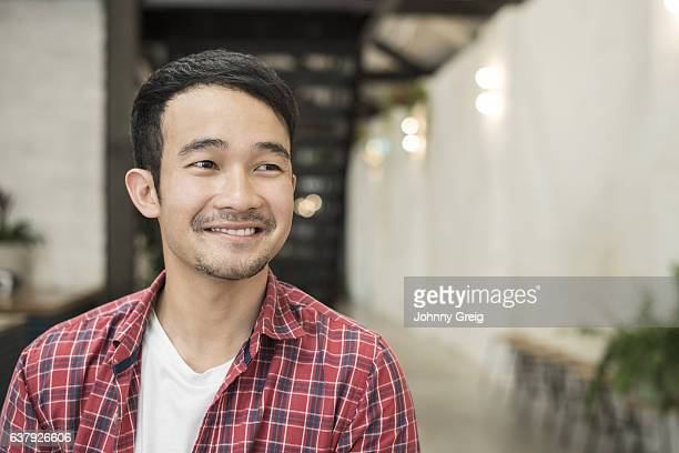 Portrait of happy young Asian man looking away and smiling