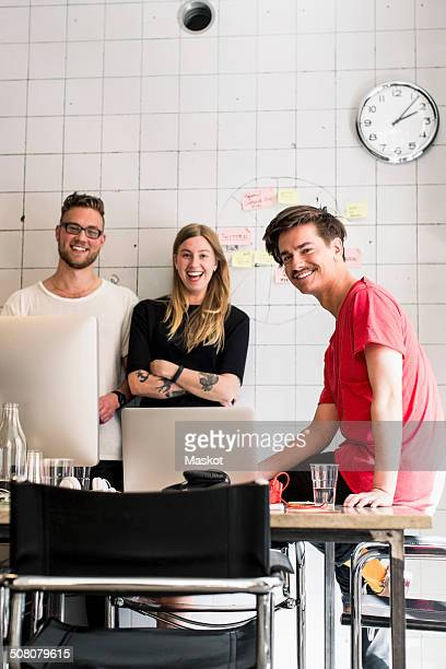 Portrait of happy young business people in creative office