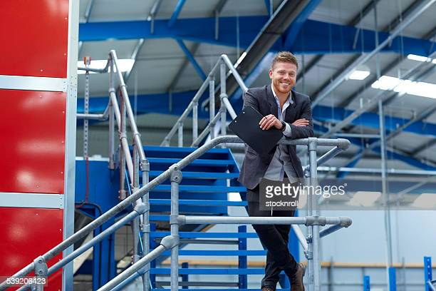 Portrait of happy young businessman in factory