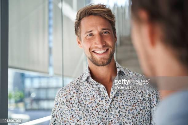 portrait of happy young businessman looking at colleague - buntes hemd stock-fotos und bilder