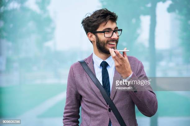 Portrait of happy young businessman on the phone outdoors