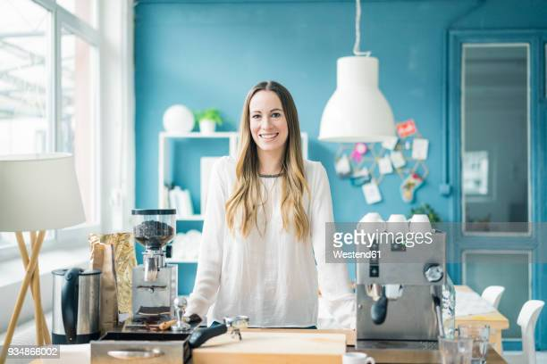 Portrait of happy young businesswoman in kitchen of a loft