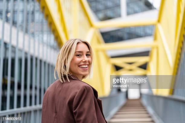portrait of happy young businesswoman on a bridge in the city - tourner photos et images de collection