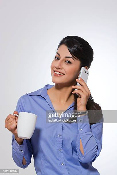 Portrait of happy young businesswoman with coffee mug answering phone over gray background