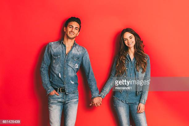 Portrait of happy young couple holding hands in front of red background