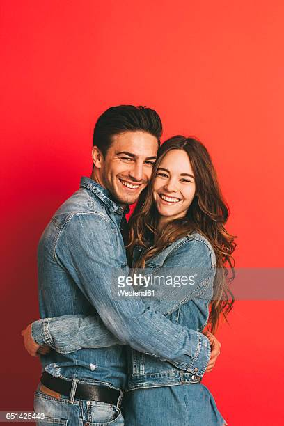 portrait of happy young couple hugging each other in front of red background - heteroseksueel koppel stockfoto's en -beelden