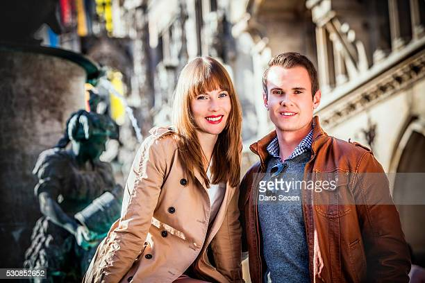 Portrait of happy young couple on Marienplatz, Munich, Bavaria, Germany