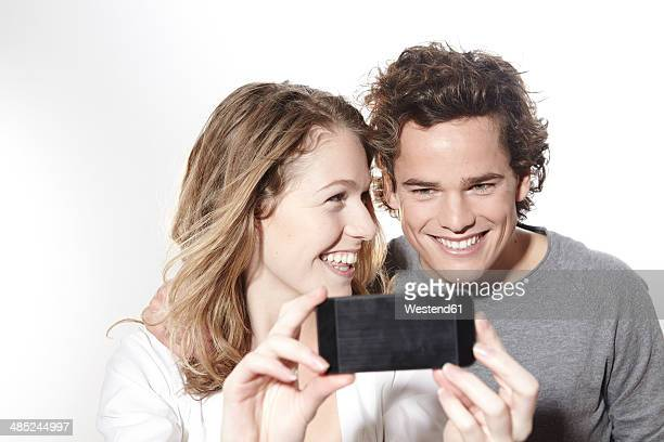 Portrait of happy young couple with smart phone, studio shot