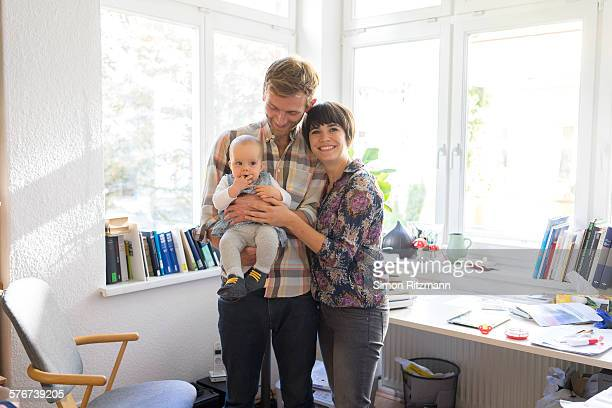 Portrait of happy young family with baby daughter.