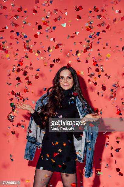 Portrait of happy young fashionable woman standing amidst confetti against coral background