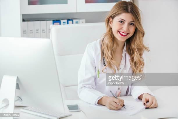 診断を書いて幸せな若いフレンドリーな医者の肖像画