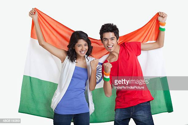 portrait of happy young friends cheering while holding indian flag over white background - indian flag stock pictures, royalty-free photos & images