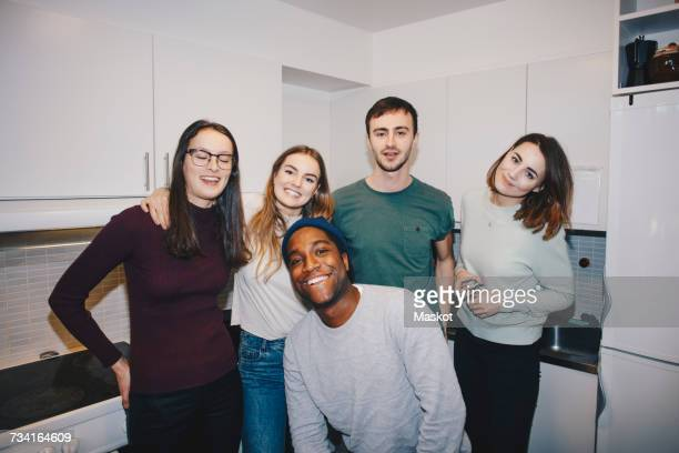 Portrait of happy young friends standing in kitchen at college dorm