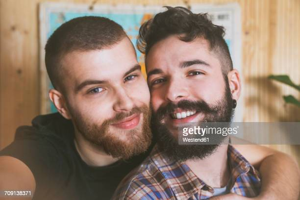 Portrait of happy young gay couple taking selfie